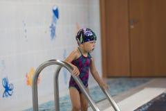 Bambino che entra nella piscina fotografia stock libera da diritti