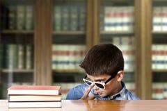 Bambino che esamina i libri Immagini Stock Libere da Diritti