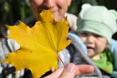Bambino che esamina la foglia di acero gialla in mano della madre fotografie stock