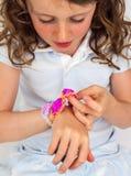 bambino che esamina un braccialetto elastico colourful Fotografia Stock