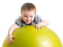 Bambino che fa esercizio di forma fisica sulla palla di forma fisica Immagini Stock Libere da Diritti