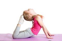 Bambino che fa gli esercizi di forma fisica sulla stuoia Isolato su bianco immagine stock