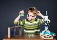 Bambino che fa gli esperimenti di scienza Scienziato sporco divertente pazzo Edu immagine stock
