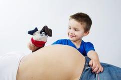 Bambino che fa i fronti e che gioca sopra la pancia di sua madre incinta Fotografia Stock