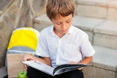 Bambino che fa il suo compito all'aperto dopo la scuola Fotografia Stock
