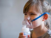 Bambino che fa inalazione con la maschera sul suo fronte Concetto di problemi di asma fotografie stock libere da diritti