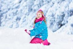 Bambino che fa pupazzo di neve Gioco dei bambini in neve nell'inverno immagini stock libere da diritti