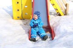 Bambino che fa scorrere sul campo da giuoco nell'inverno Immagine Stock