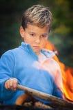 Bambino che fissa al fuoco di accampamento Fotografie Stock Libere da Diritti