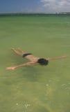 Bambino che galleggia nella laguna di paradiso fotografia stock libera da diritti