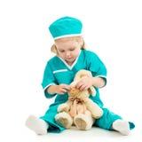 Bambino che gioca al dottore e che cura giocattolo immagini stock