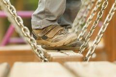 Bambino che gioca alle attrazioni delle oscillazioni, primo piano delle gambe Fotografia Stock