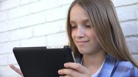 Bambino che gioca compressa, bambino Smartphone, messaggi della lettura della ragazza che passano in rassegna Internet stock footage