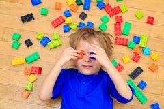 Bambino che gioca con i blocchi di plastica variopinti dell'interno Fotografia Stock Libera da Diritti