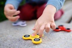 Bambino che gioca con i filatori giranti popolari di irrequietezza Fotografia Stock