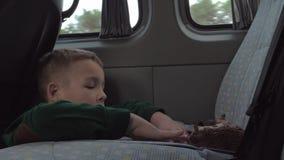 Bambino che gioca con i giocattoli durante il viaggio dell'automobile stock footage