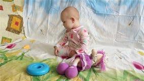 Bambino che gioca con i giocattoli e che esamina la macchina fotografica stock footage