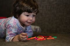 Bambino che gioca con i piccoli giocattoli sullo strato nella sala immagine stock