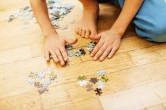 Bambino che gioca con i puzzle sul pavimento di legno insieme al genitore, concetto della gente di stile di vita, mani amorose a  fotografia stock libera da diritti