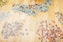 Bambino che gioca con i puzzle sul pavimento di legno insieme al genitore, concetto della gente di stile di vita, mani amorose a  fotografia stock