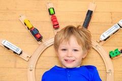 Bambino che gioca con i treni dell'interno Fotografie Stock