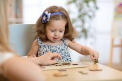 Bambino che gioca con il giocattolo di puzzle dell'interno Immagini Stock