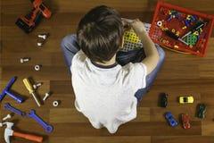 Bambino che gioca con il kit di utensili dei giocattoli mentre sedendosi sul pavimento nella sua stanza Vista superiore fotografia stock