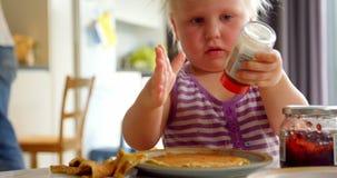 Bambino che gioca con il pepe sul tavolo da pranzo 4k archivi video