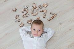Bambino che gioca con il ` s EVE del nuovo anno del pan di zenzero Fotografie Stock Libere da Diritti