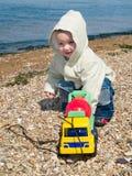 Bambino che gioca con l'automobile sulla spiaggia Fotografia Stock