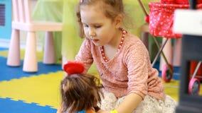 Bambino che gioca con la bambola sul campo da giuoco Giochi della neonata nei giochi per i bambini Gioco della figlia della madre video d archivio