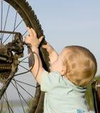 Bambino che gioca con la rotella della bici Fotografia Stock Libera da Diritti