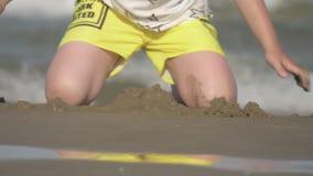 Bambino che gioca con la sabbia alla spiaggia archivi video