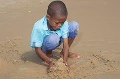 Bambino che gioca con la sabbia bagnata immagine stock libera da diritti