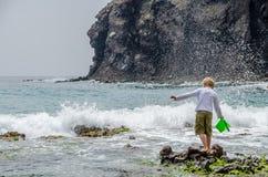 Bambino che gioca con le onde di marzo Mediterraneo Fotografia Stock Libera da Diritti