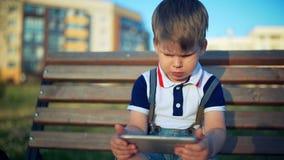 Bambino che gioca con lo Smart Phone nel parco all'aperto stock footage