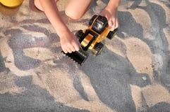 Bambino che gioca con un trattore del giocattolo sulla spiaggia fotografie stock libere da diritti