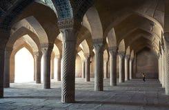 Bambino che gioca fra le colonne di Shabestan dentro la moschea di Vakil di Shiraz Immagini Stock