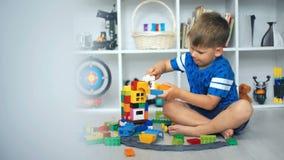Bambino che gioca i blocchetti del giocattolo nella stanza bianca video d archivio