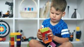 Bambino che gioca i blocchetti del giocattolo nella stanza bianca archivi video