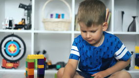 Bambino che gioca i blocchetti del giocattolo nella stanza bianca stock footage