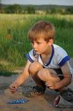 Bambino che gioca i marmi Immagini Stock Libere da Diritti