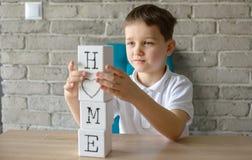 Bambino che gioca i mattoni di legno con le lettere che fanno la casa di parola Immagini Stock