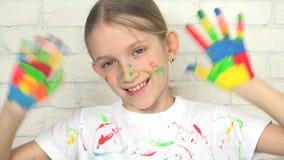 Bambino che gioca le mani dipinte, bambino che guarda in camera, fronte sorridente della ragazza della scuola archivi video