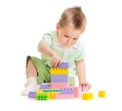 Bambino che gioca le particelle elementari variopinte del giocattolo Fotografie Stock Libere da Diritti