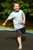 Bambino che gioca mentre saltando sul trampolino all'aperto fotografia stock libera da diritti