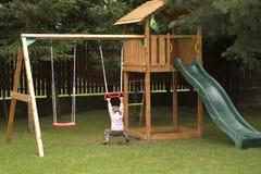 Bambino che gioca nel campo da giuoco Fotografie Stock
