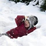 Bambino che gioca nella neve fotografie stock