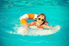 Bambino che gioca nella piscina fotografia stock libera da diritti