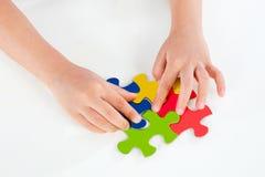 Bambino che gioca puzzle variopinto Fotografia Stock